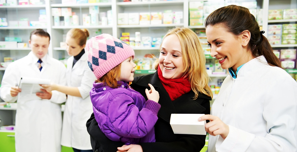 pharmacist smiling on a woman carrying her child